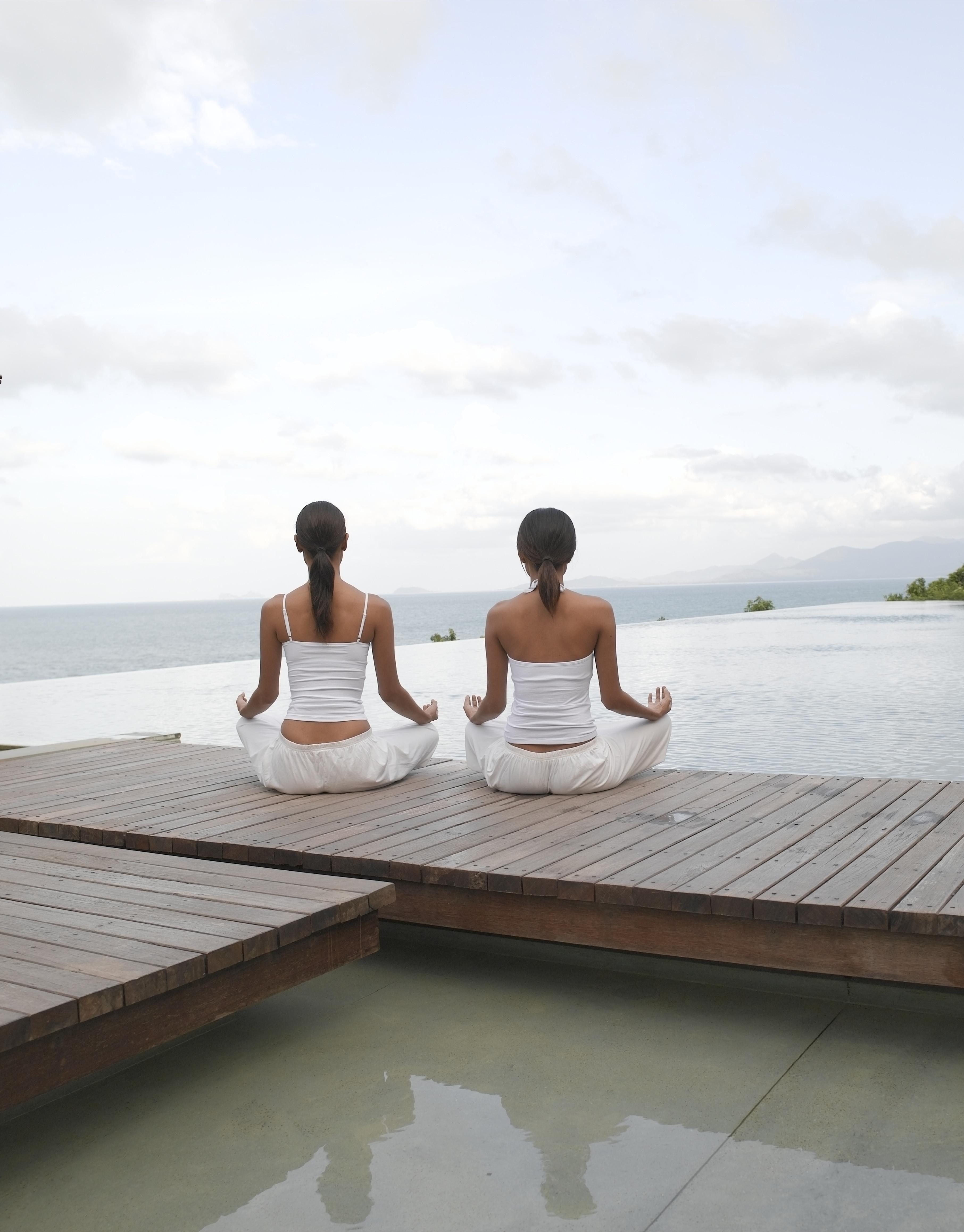 Two women meditating on boardwalk facing ocean, rear view